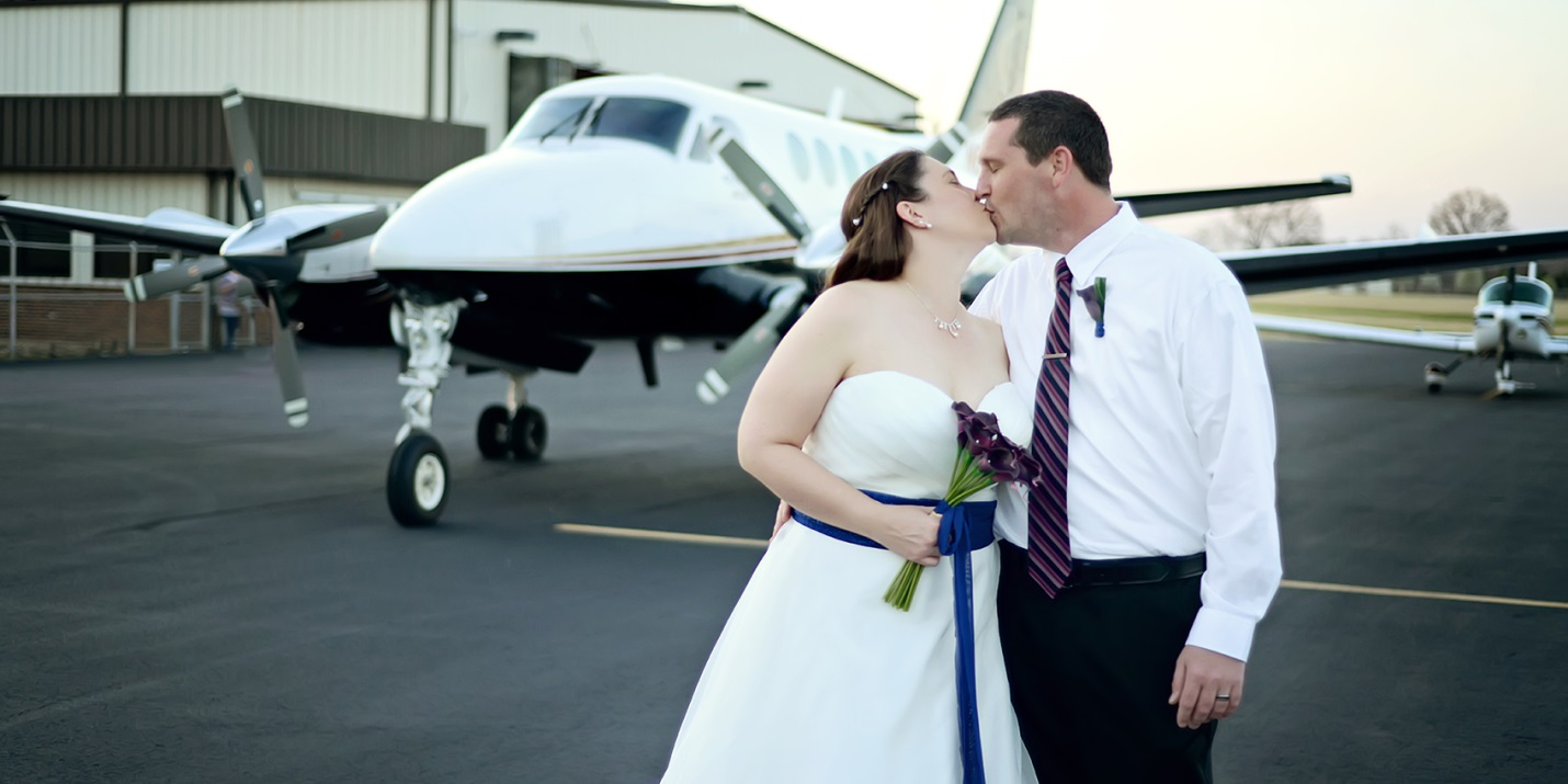 Newly married couple kiss in front of a King Air