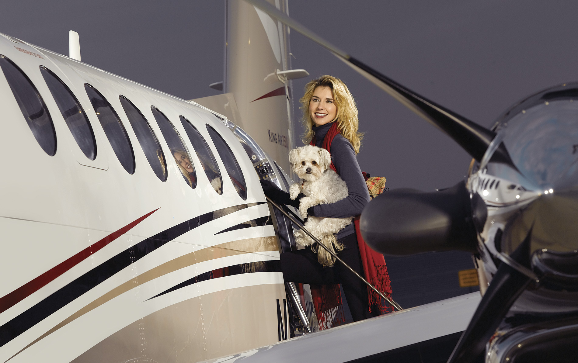Woman boarding a King Air with a small pet